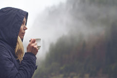 Femme buvant une tasse de café dans l'arrangement extérieur photo stock