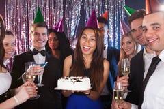 Femme célébrant l'anniversaire avec des amis à la boîte de nuit Image libre de droits