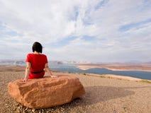 Femme célibataire méditant devant un lac Images libres de droits