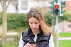 Femme célibataire marchant et regardant vers le bas le téléphone Image stock