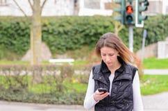 Femme célibataire marchant et regardant vers le bas le téléphone Photographie stock libre de droits