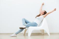 Femme célibataire s'asseyant sur la chaise blanche Image libre de droits
