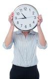 Femme cachant son visage derrière l'horloge murale Image stock