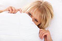 Femme cachant son visage sous la feuille Images stock
