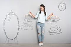 Femme calme se tenant près du miroir et rêvant de nouveaux vêtements photos stock