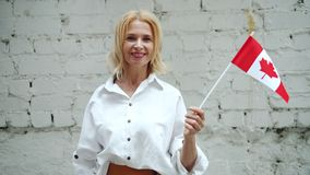Femme canadienne mûre tenant le drapeau national du Canada sur le fond de mur de briques clips vidéos