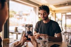 Femme capturant des photos d'hamburger mangeur d'hommes Photos stock