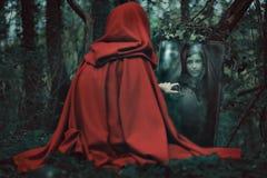 Femme à capuchon mystérieuse devant un miroir magique Images stock