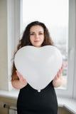 Femme caucasienne attirante tenant un coeur de baloon Photos stock