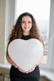 Femme caucasienne attirante tenant un coeur de baloon Photographie stock libre de droits