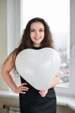 Femme caucasienne attirante tenant un coeur de baloon Photos libres de droits