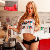 Femme caucasienne avec du charme faisant cuire une soupe Photographie stock
