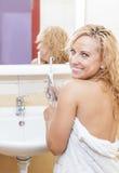 Femme caucasienne avec la brosse à dents électrique moderne dans la salle de bains Images libres de droits