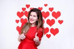 Femme caucasienne blanche avec les lèvres rouges renonçant à des pouces et souriant sur le fond en forme de coeur ` S de Valentin Image libre de droits