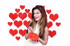 Femme caucasienne blanche avec les lèvres rouges tenant un cadeau à une main et à arrière-plan en forme de coeur de sourire Conce Photo libre de droits