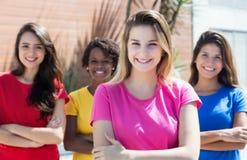 Femme caucasienne blonde avec trois amies dans la ville Images stock