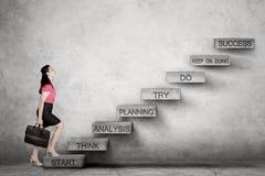 Femme caucasienne d'affaires recherchant prête à monter l'escalier de succès Photo libre de droits