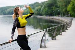 Femme caucasienne d'athlète en eau potable de vêtements de sport après sport Images stock