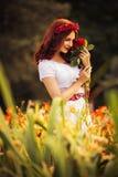Femme caucasienne de brune dans la robe blanche au parc en fleurs rouges et jaunes sur un coucher du soleil d'été tenant des rose Images stock