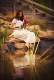Femme caucasienne de brune dans la robe blanche au parc en fleurs rouges et jaunes sur un coucher du soleil d'été tenant des rose Photo libre de droits