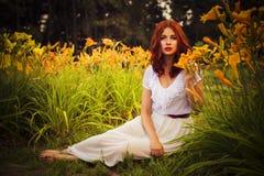 Femme caucasienne de brune dans la robe blanche au parc en fleurs rouges et jaunes sur un coucher du soleil d'été tenant des fleu Image stock