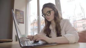 Femme caucasienne de brune dans le fonctionnement en verre dans un café avec l'ordinateur portable, 4K clips vidéos