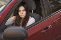 Femme caucasienne de jeune belle brune conduisant une voiture rouge somme Images stock