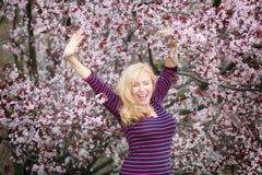Femme caucasienne de longs cheveux blonds heureuse et riante près de l'arbre de floraison images libres de droits