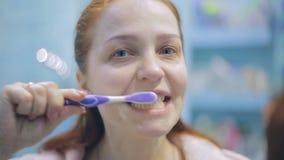 Femme caucasienne de mode de vie avec les cheveux rouges se brossant les dents dans la salle de bains, soins de santé banque de vidéos
