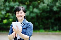 Femme caucasienne de sourire à l'aide de l'ordinateur de comprimé Photographie stock
