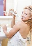 Femme caucasienne de sourire heureuse avec la brosse à dents électrique moderne dans la salle de bains Image stock