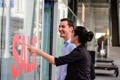 Femme caucasienne et homme excités quand voyez le prix à payer en mode d'habillement de vente au magasin Images libres de droits