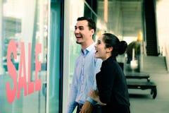Femme caucasienne et homme excités quand voyez le prix à payer en vente au magasin Photos libres de droits