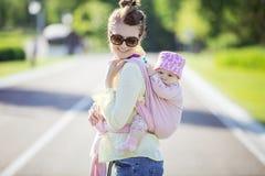 Femme caucasienne gaie portant sa fille de bébé sur le dos image stock