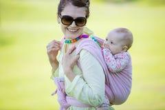 Femme caucasienne gaie portant sa fille de bébé sur le parc de dos au printemps images libres de droits