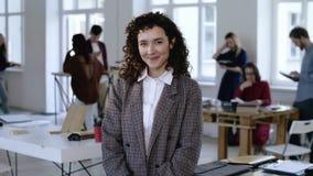 Femme caucasienne heureuse d'affaires de patron portant le costume formel élégant, souriant avec le regard gai au fond moderne de clips vidéos