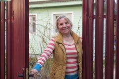Femme caucasienne mûre ouvrant la barrière rouge pour accueillir quelques invités photo libre de droits