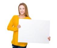 Femme caucasienne montrant un conseil blanc image stock