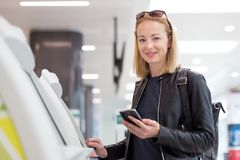 Femme caucasienne occasionnelle à l'aide de la machine intelligente d'application et d'enregistrement de téléphone à l'aéroport o Images libres de droits