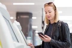 Femme caucasienne occasionnelle à l'aide de la machine intelligente d'application et d'enregistrement de téléphone à l'aéroport o Photo stock