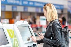Femme caucasienne occasionnelle à l'aide de la machine intelligente d'application et d'enregistrement de téléphone à l'aéroport o Image stock
