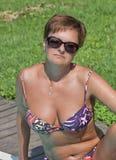 Femme caucasienne s'asseyant après la natation dans la piscine extérieure Photographie stock libre de droits