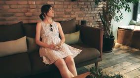Femme caucasienne seule dans la robe attendant sa date dans un café banque de vidéos