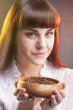 Femme caucasienne tenant la tasse en bois avec des grains de café de Brown Photographie stock libre de droits