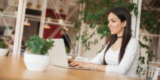 Femme causant avec des amis à l'aide de l'ordinateur portable avec l'Internet sans fil Image libre de droits
