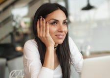 Femme causant avec des amis à l'aide de l'ordinateur portable avec l'Internet sans fil Photographie stock libre de droits