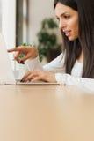 Femme causant avec des amis à l'aide de l'ordinateur portable avec l'Internet sans fil Photos stock