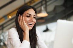 Femme causant avec des amis à l'aide de l'ordinateur portable avec l'Internet sans fil Photo stock
