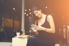 Femme causant avec ses amis par téléphone de cellules pendant le petit déjeuner dans la boutique de coffe Images libres de droits