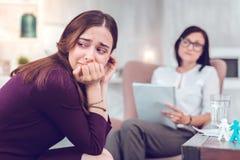 Femme châtain douleureuse bouleversée pleurant tout en rendant visite à un phycologue photos stock